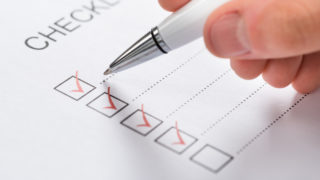Close-up Of Silver Pen Over Filled Checkboxes In Form